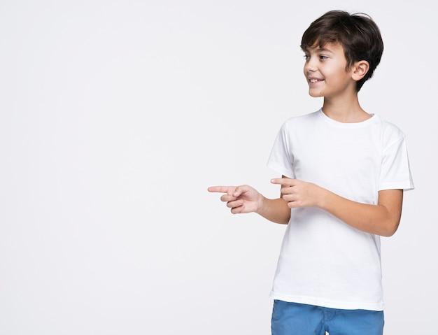 Giovane ragazzo che indica con lo spazio della copia Foto Gratuite