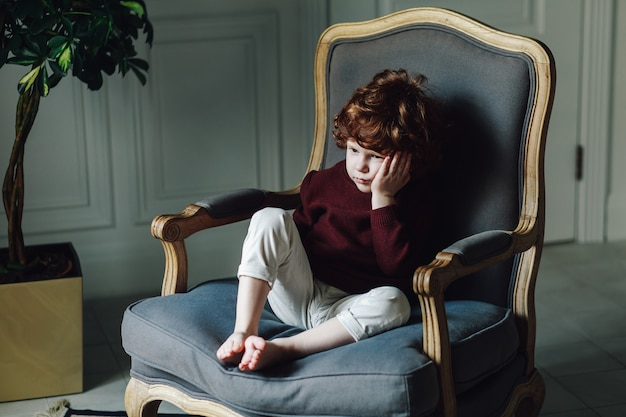 Giovane ragazzo che si appoggia sulla sua mano mentre era seduto in poltrona. sembra pensieroso e un po 'triste Foto Premium