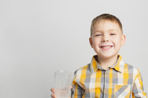 Giovane ragazzo che sorride e che tiene il vetro di latte Foto Gratuite