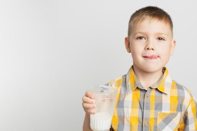 Giovane ragazzo che tiene bicchiere di latte Foto Gratuite
