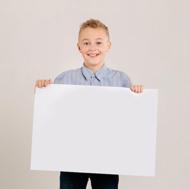 Giovane ragazzo che tiene carta in bianco Foto Gratuite