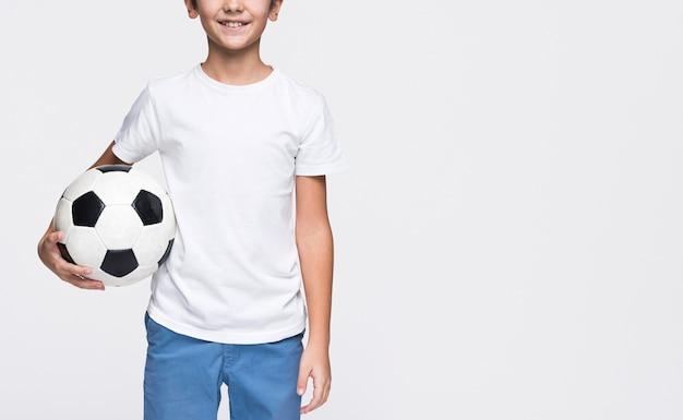 Giovane ragazzo del primo piano con la sfera di calcio Foto Gratuite