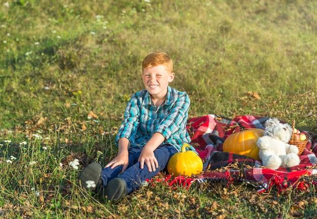 Giovane ragazzo di smiley che si siede su una coperta di picnic Foto Gratuite