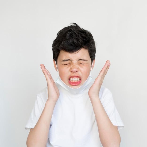 Giovane ragazzo di vista frontale che starnutisce Foto Gratuite