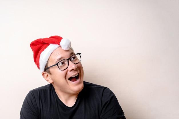 Giovane ragazzo divertente con il cappello di natale sulla parete bianca. santa triste. natale Foto Premium