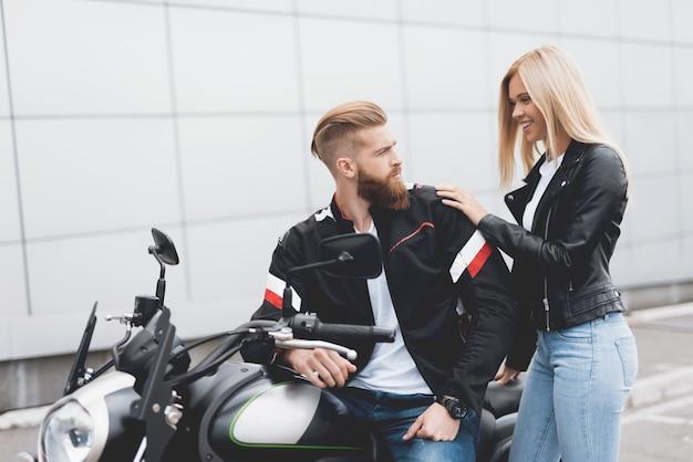Giovane ragazzo e ragazza che si siede su una moderna moto elettrica Foto Premium