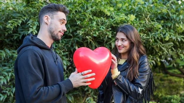 Giovane ragazzo e signora sorridente con palloncino a forma di cuore Foto Gratuite