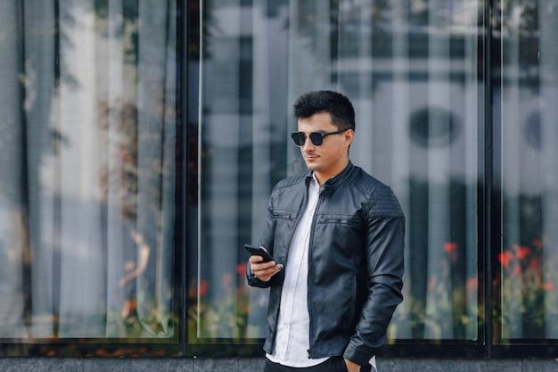 Giovane ragazzo elegante con gli occhiali in giacca di pelle nera con telefono Foto Gratuite