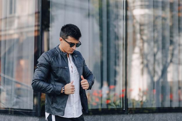 Giovane ragazzo elegante con gli occhiali in giacca di pelle