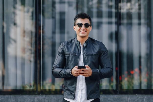Giovane ragazzo elegante in bicchieri in giacca di pelle nera con telefono sulla superficie del vetro Foto Gratuite