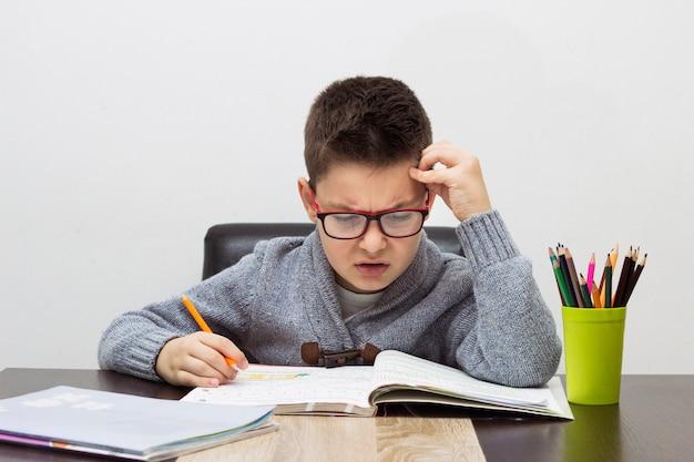 Giovane ragazzo frustrato per i compiti, scrivendo a casa. ragazzo, studiare, tavola. disegno del bambino con una matita. Foto Gratuite
