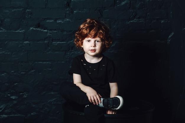 Giovane ragazzo riccio sveglio in abbigliamento casual scuro che si siede con le gambe attraversate Foto Premium