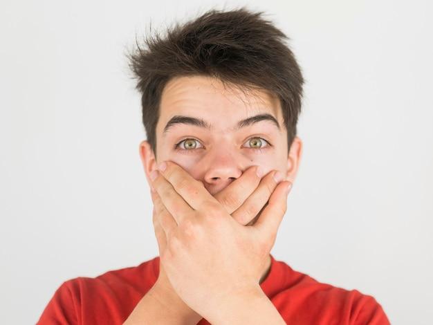 Giovane ragazzo sveglio in maglietta rossa che è messa a tacere Foto Gratuite