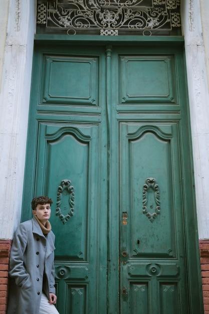 Giovane ragazzo vicino a una grande porta d'ingresso Foto Gratuite
