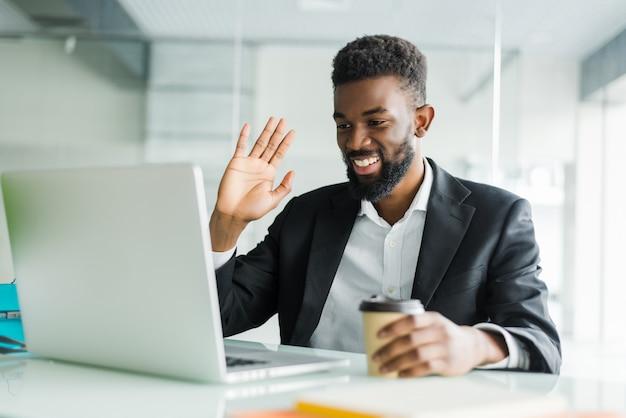 Giovane responsabile afroamericano con stoppia che si siede davanti alle cuffie d'uso del computer portatile aperto mentre avendo videoconferenza con i soci commerciali Foto Gratuite