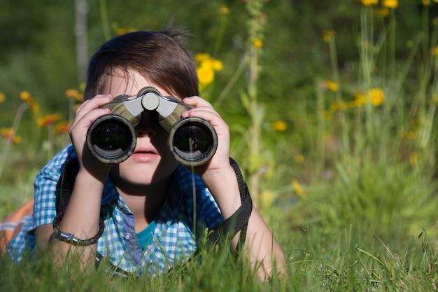 Giovane ricercatore del ragazzo che esplora con l'ambiente del binocolo nel giardino di estate Foto Premium