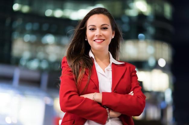 Giovane ritratto della donna di affari in una regolazione moderna della città alla notte Foto Premium