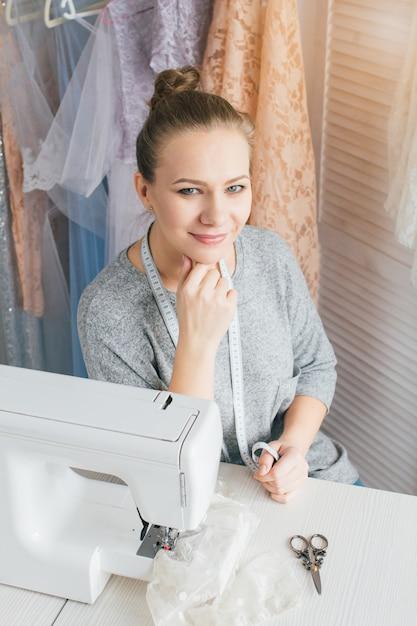 Giovane sarta che lavora alla macchina per cucire Foto Premium