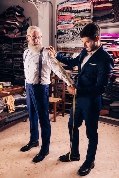 Giovane sarto maschio che prende misura delle maniche dell'uomo senior nel negozio Foto Gratuite