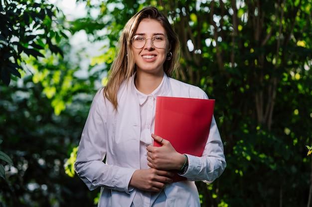 Giovane scienziata che posa con la cartella rossa Foto Gratuite