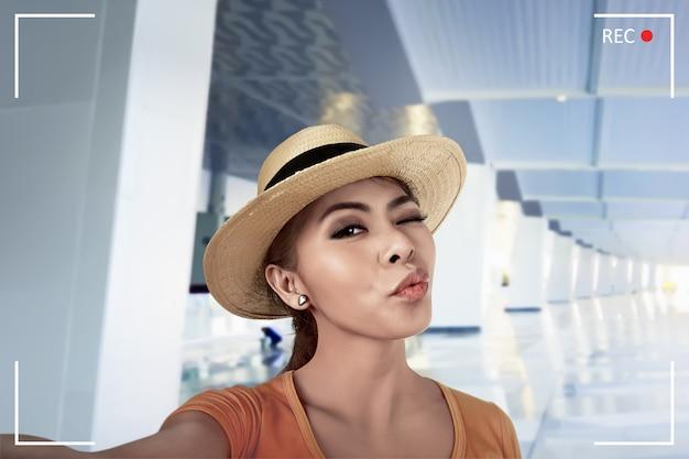 Giovane selfie asiatico di posa della donna nella lobby dell'aeroporto Foto Premium