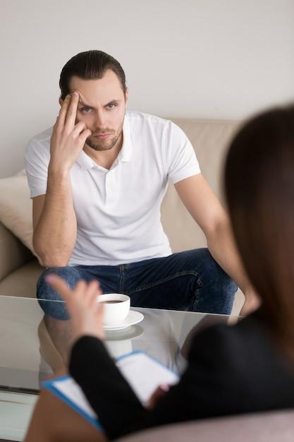 Giovane serio che ascolta psicologo, consulente o consulente femminile Foto Gratuite