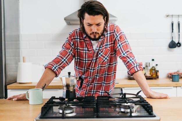 Giovane serio che prepara caffè in cucina Foto Gratuite