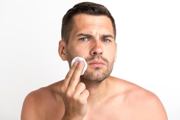 Giovane serio che pulisce il suo fronte contro il fondo bianco Foto Gratuite