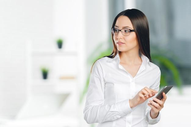 Giovane, sicura, riuscita e bella donna di affari con il telefono cellulare isolato Foto Premium