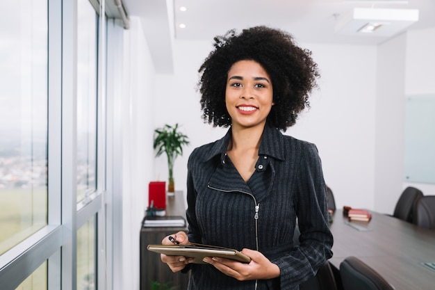 Giovane signora afroamericana felice con i documenti vicino alla finestra Foto Gratuite