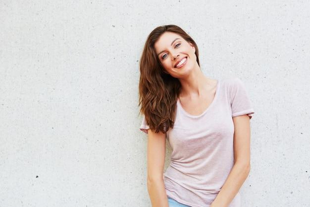 b00a40e5bdc1 Giovane signora attraente che sorride contro la priorità bassa ...
