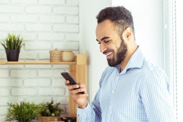 Giovane smart phone africano bello della tenuta Foto Premium