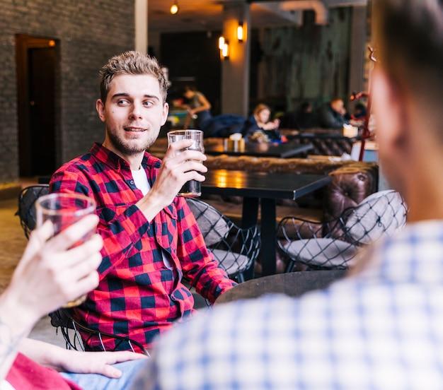 Giovane sorridente che beve la birra con i suoi amici in pub Foto Gratuite