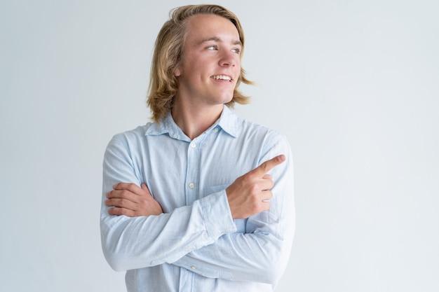 Giovane sorridente che indica il dito da parte Foto Gratuite