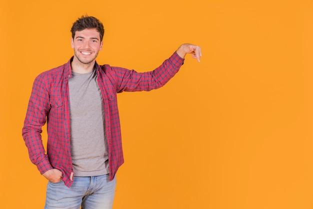 Giovane sorridente che punta il dito verso l'alto su uno sfondo arancione Foto Gratuite