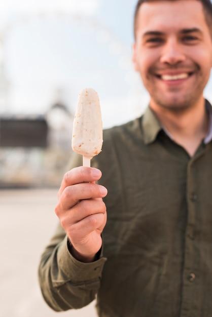 Giovane sorridente che tiene il gelato delizioso del ghiacciolo Foto Gratuite
