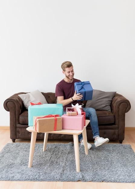 Giovane sorridente che tiene scatola attuale che si siede sul sofà a casa Foto Gratuite