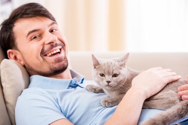 Giovane sorridente con il suo gatto sveglio sullo strato a casa. Foto Premium