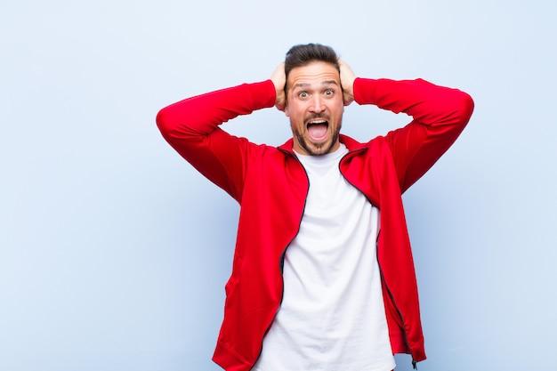 Giovane sportivo bello uomo o monitor che sembra felice, spensierato, amichevole e rilassato godendo la vita e il successo, con un atteggiamento positivo contro la parete piatta Foto Premium