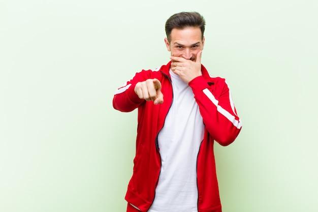 Giovane sportivo bello uomo o monitor ridere di te, indicando la fotocamera e prendendo in giro o deridendoti contro la parete piatta Foto Premium