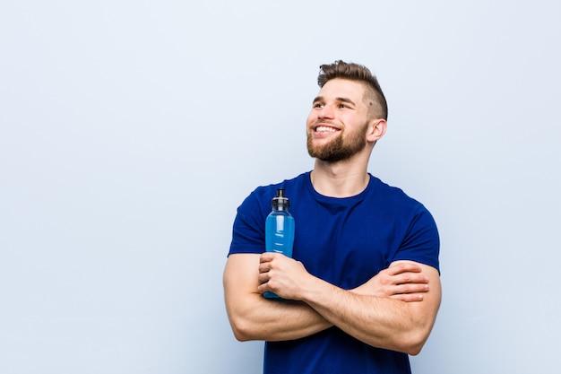 Giovane sportivo caucasico che tiene un sorridere isotonico della bevanda sicuro con le braccia attraversate. Foto Premium