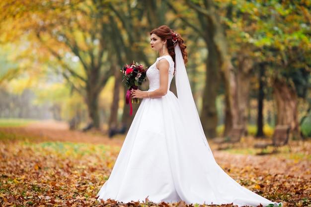 Giovane sposa in abito da sposa che cammina in un parco. abito bianco di lusso per donna. la sposa cammina nel parco. Foto Premium