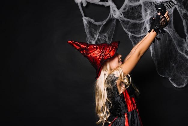 Giovane strega che tiene il pipistrello del giocattolo Foto Gratuite