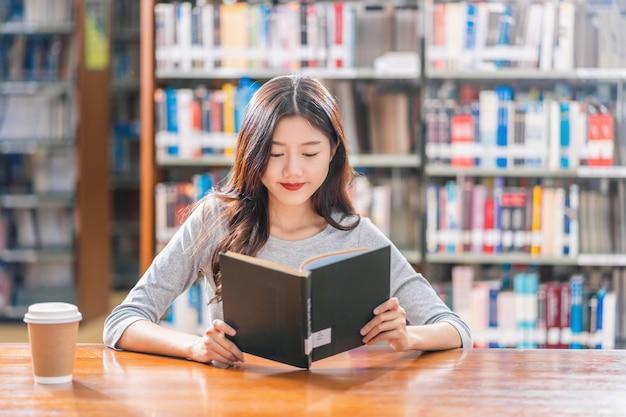 Giovane studente asiatico in vestito casuale che legge il libro con una tazza di caffè in biblioteca dell'università Foto Premium
