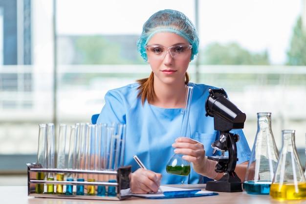 Giovane studente che lavora con soluzioni chimiche in laboratorio Foto Premium