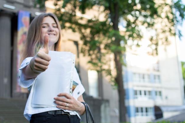 Giovane studentessa in piedi vicino all'università, con in mano una carta che sorride e che mostra come contro il college, va a scuola Foto Premium