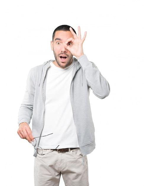 Giovane stupito che usa le sue mani come un binocolo Foto Premium