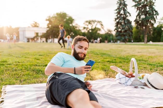 Giovane sul picnic con il canestro di frutta che esamina telefono cellulare che manda un sms nel parco Foto Premium