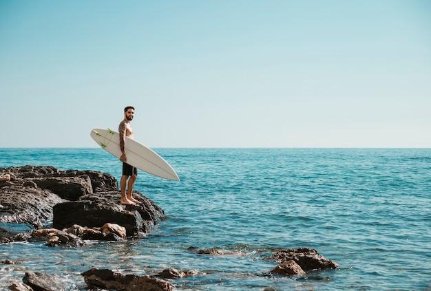 Giovane surfista in piedi sulla riva rocciosa Foto Gratuite