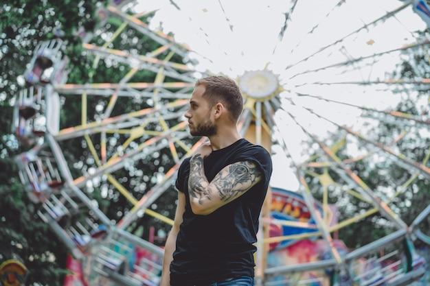 Giovane tatuato in un parco di divertimenti sullo sfondo di una giostra Foto Gratuite